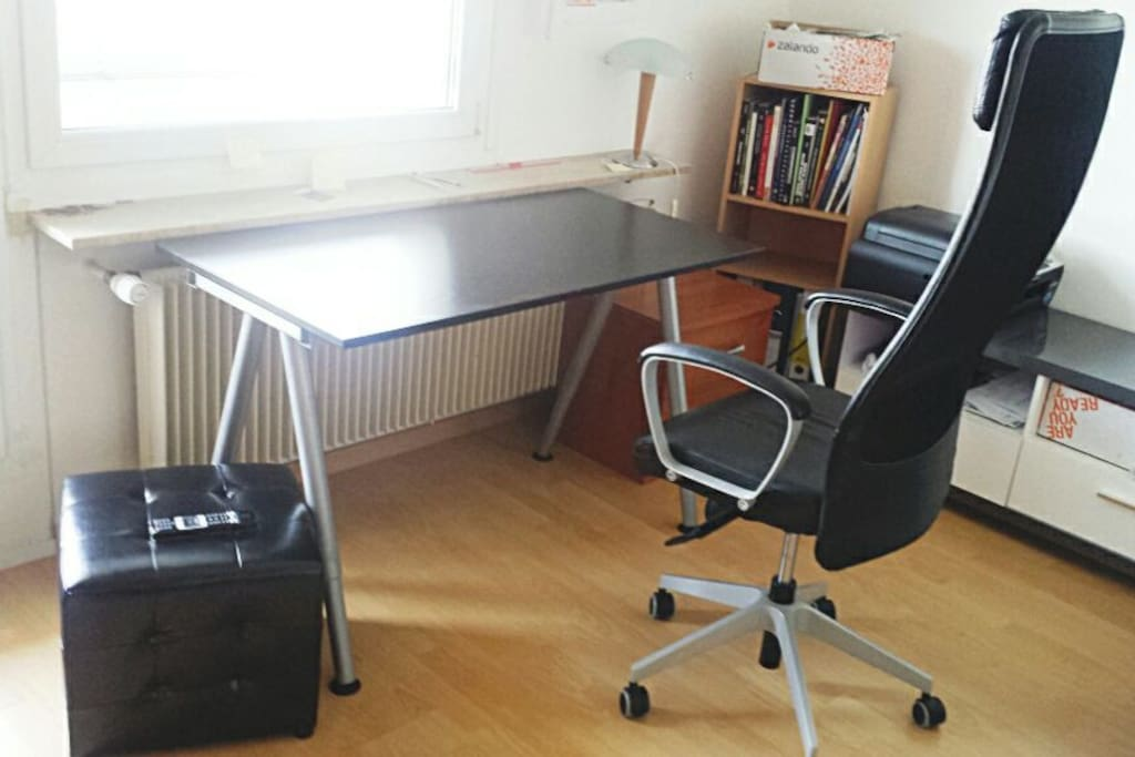 Comfortable table and chair with beautiful view via a window. It is an ideal for home office.