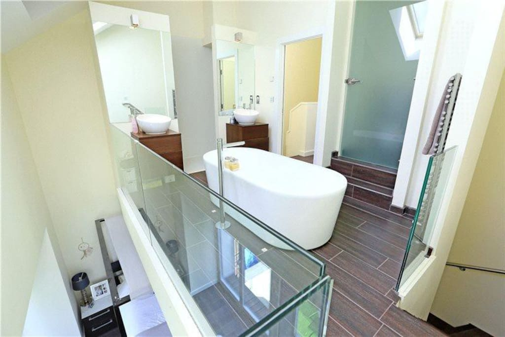 Your mezzanine ensuite bathroom with huge bath, double sinks and showers, and separate WC. It gets all the light from the floor-to-ceiling windows of the bedroom.