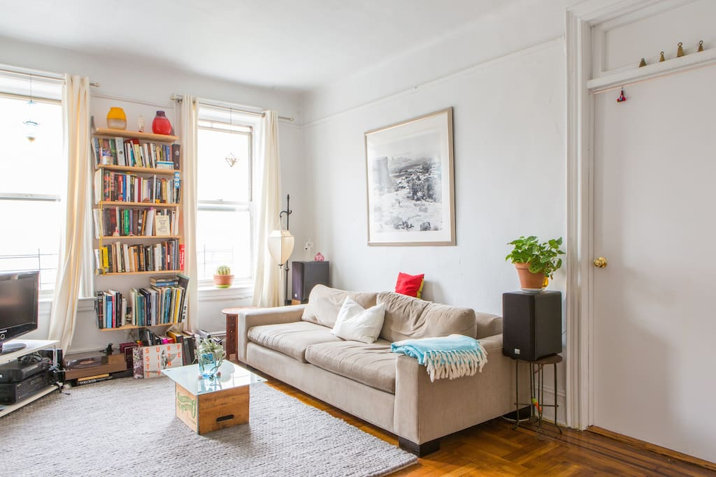 Sunny, spacious living room with large, cozy couch. Amazing library of art books to keep you inspired for nights in!