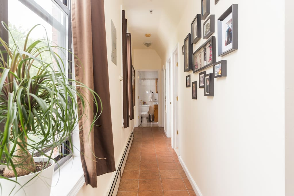 Hallway as viewed from front door. Full bathroom is at the end of the hall. Bedrooms and half bath are off to the right.