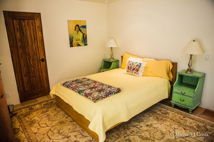 Queen bedroom with various antiques and embroideries