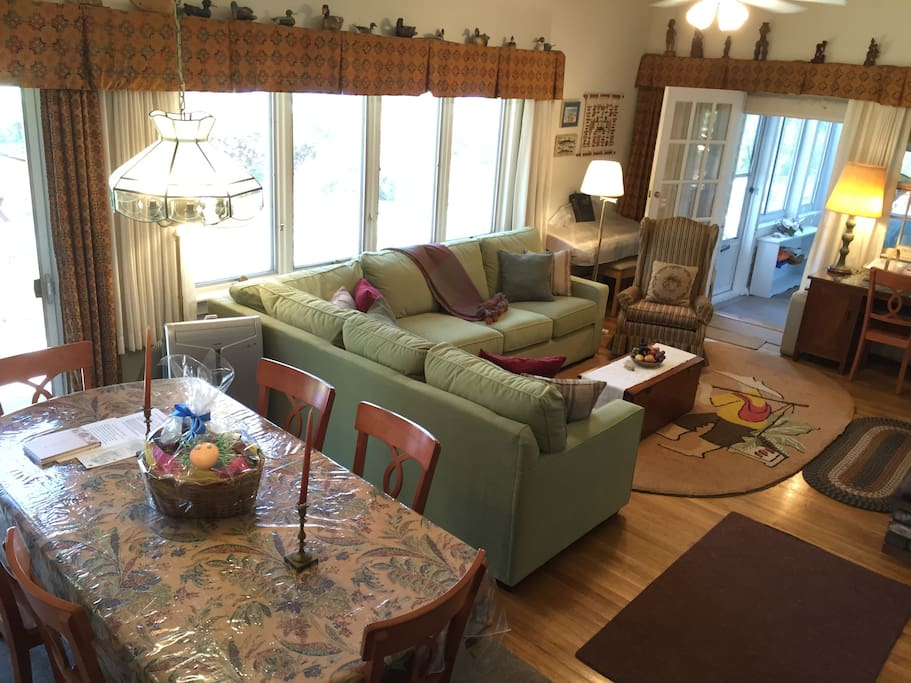 Living room with view of water and door to sunroom