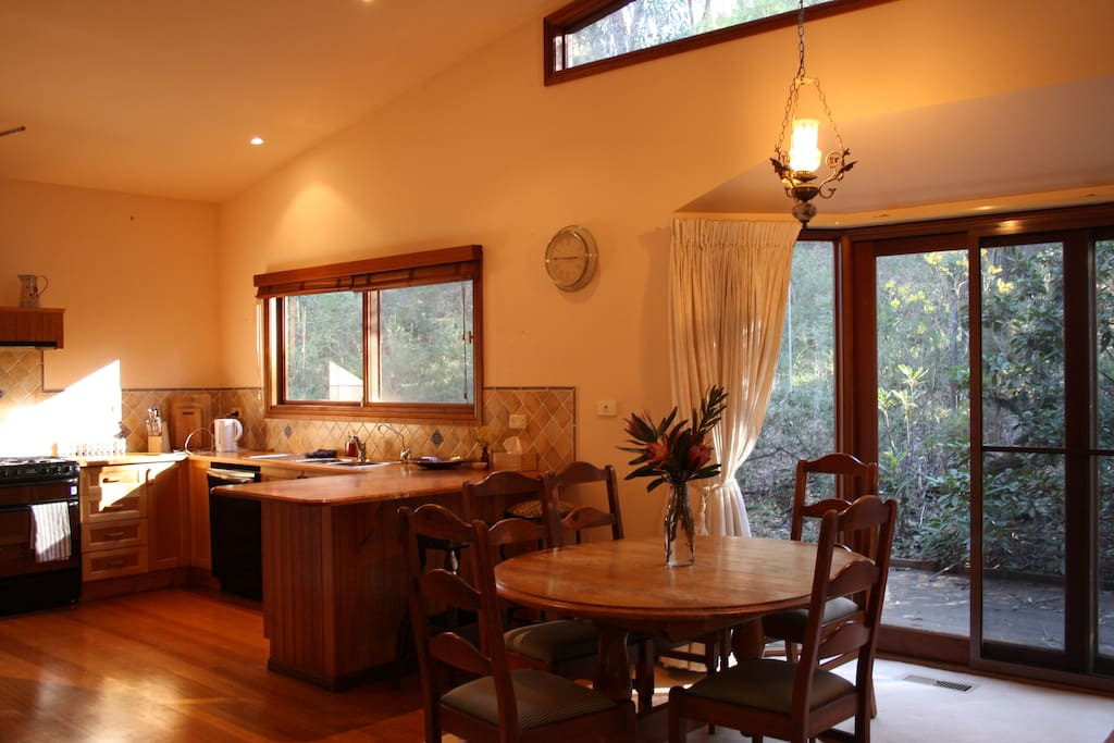 Open lounge/dining room with double windows that stretch onto a back deck.