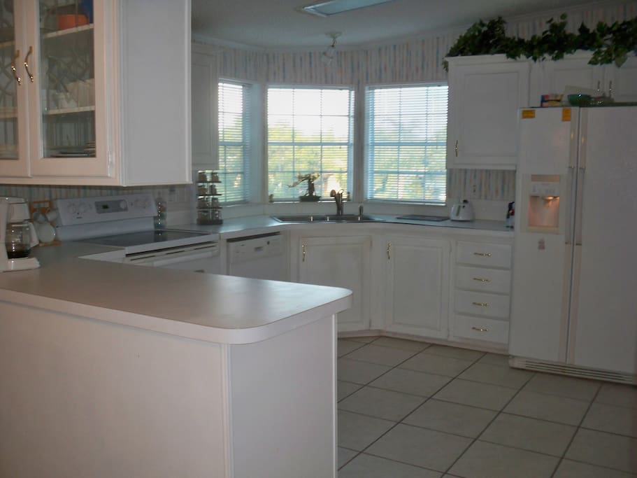 Huge bright kitchen showing a good portion of the cabinets etc.