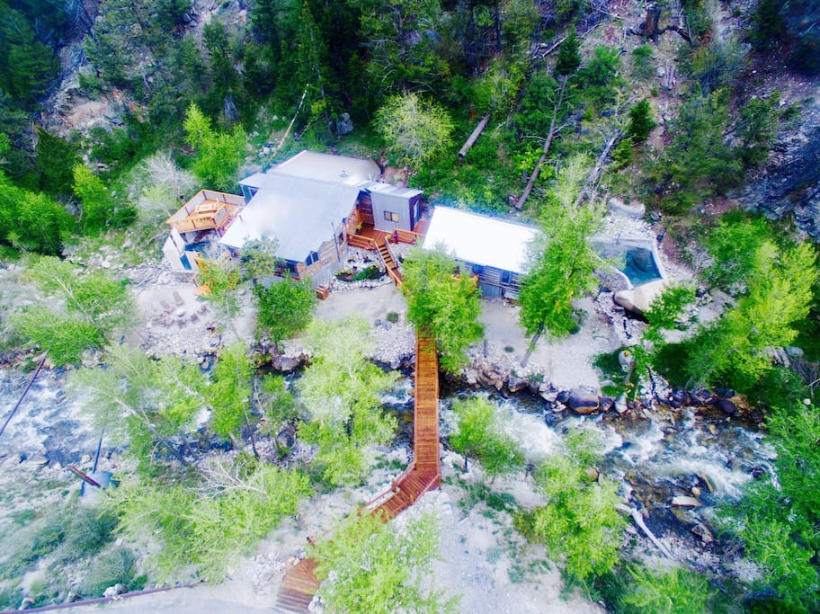 Aerial view of both cabins on the banks of Cottonwood Creek: Merrifield Cabin to the left of the bridge and Holloway Cabin to the right