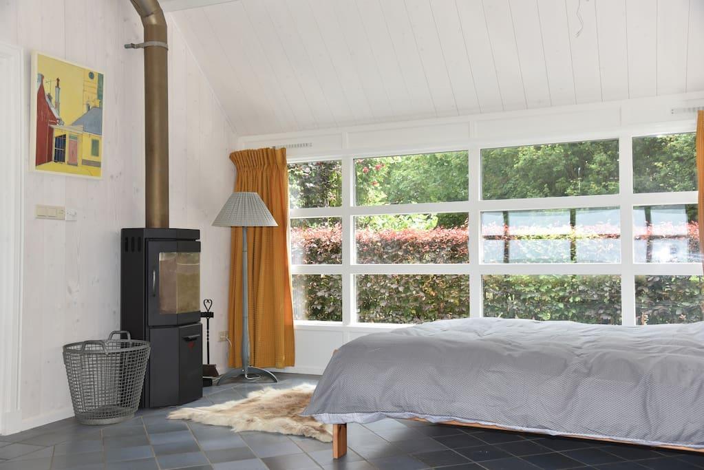 Tweepersoonsbed, houtkachel, uitzicht op de tuin.