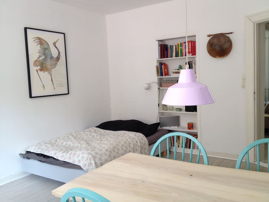 Light streetview room with table and queensize bed