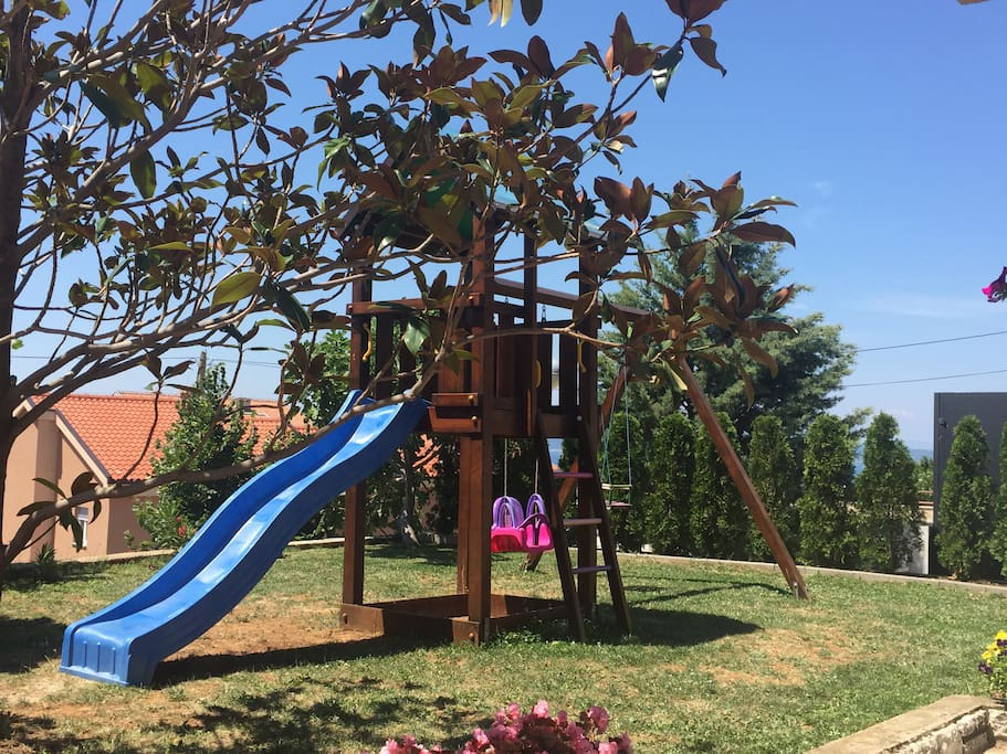 A swing set in the front yard for young children to enjoy.