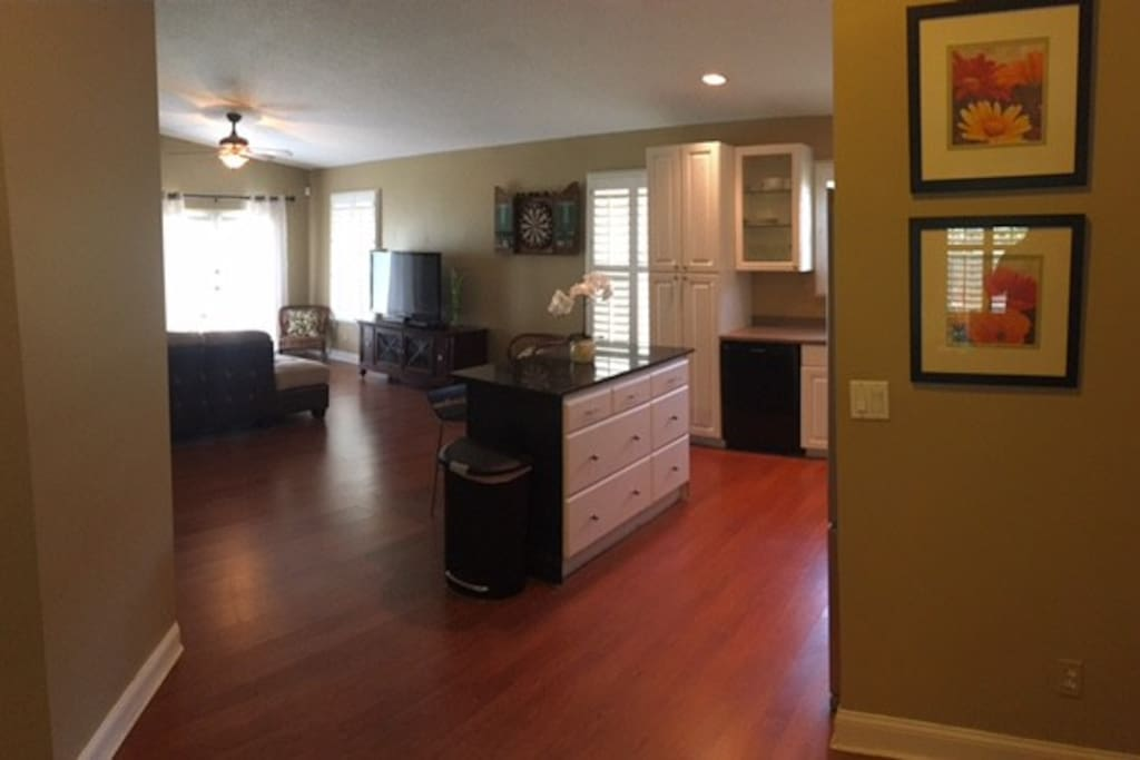 Expansive open kitchen and modern living room with large smart TV.
