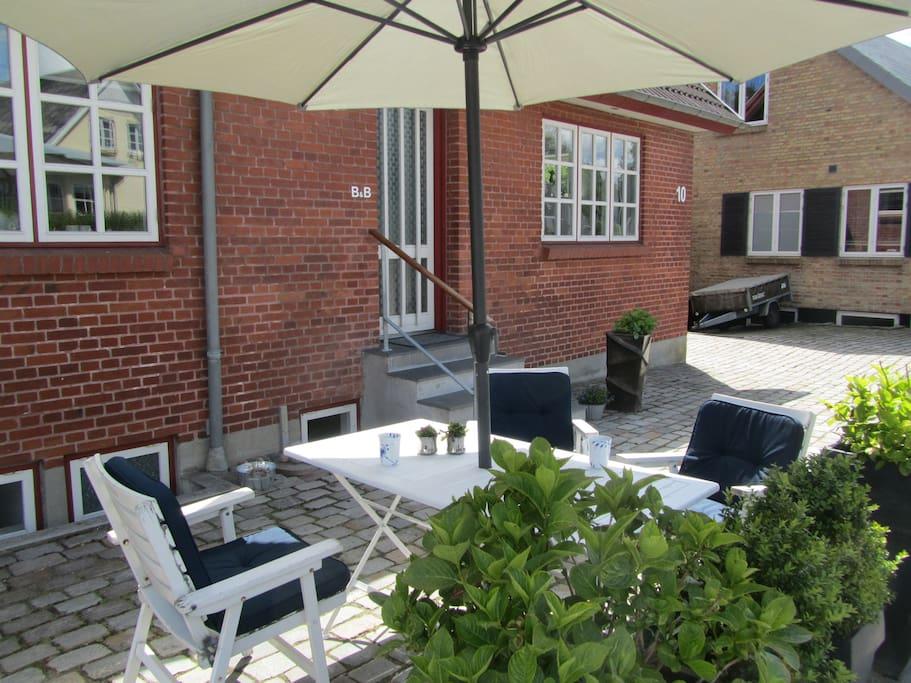 Husets front, med udendørs siddepladser.