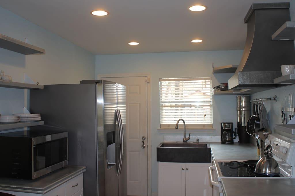 Newly remodeled kitchen. Fully equipped. We have pots and pans, an oven, microwave, large refridgerator, custom metal vent hood, zinc countertops and matching shelving.
