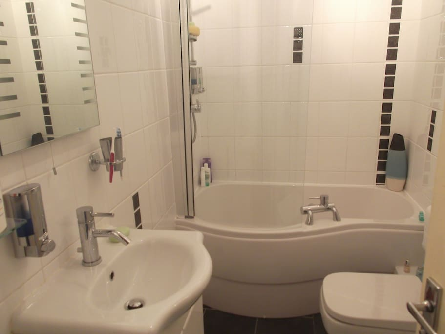 Small bathroom with curved bath & overhead shower. Heated towel rail