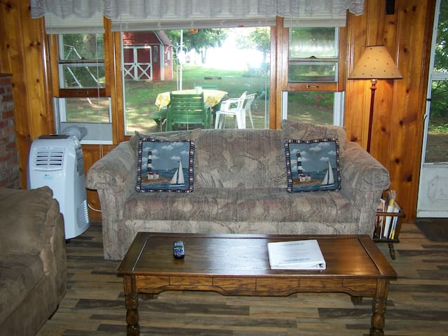 Living room has a view of Lake Huron with a sleeper sofa and air conditioner