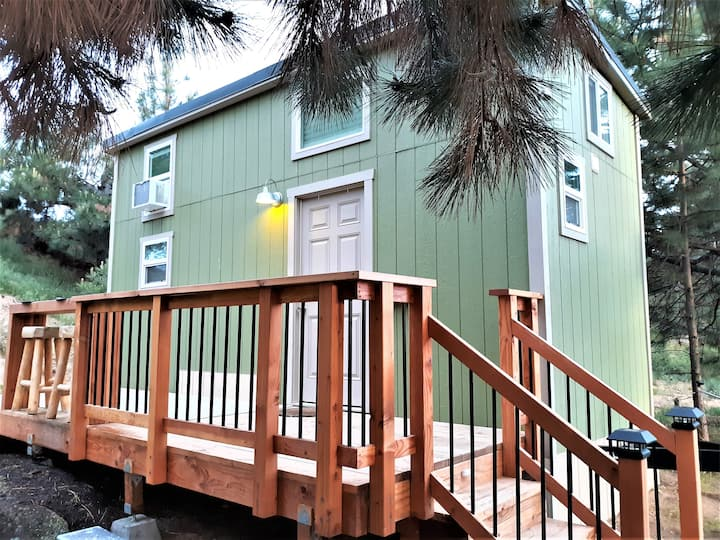 exterior view of a green tiny house with a deck