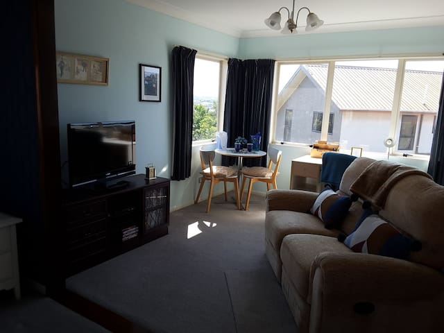 Upstairs queen bedroom/studio tv, double lazyboy couch, desk and cafe table