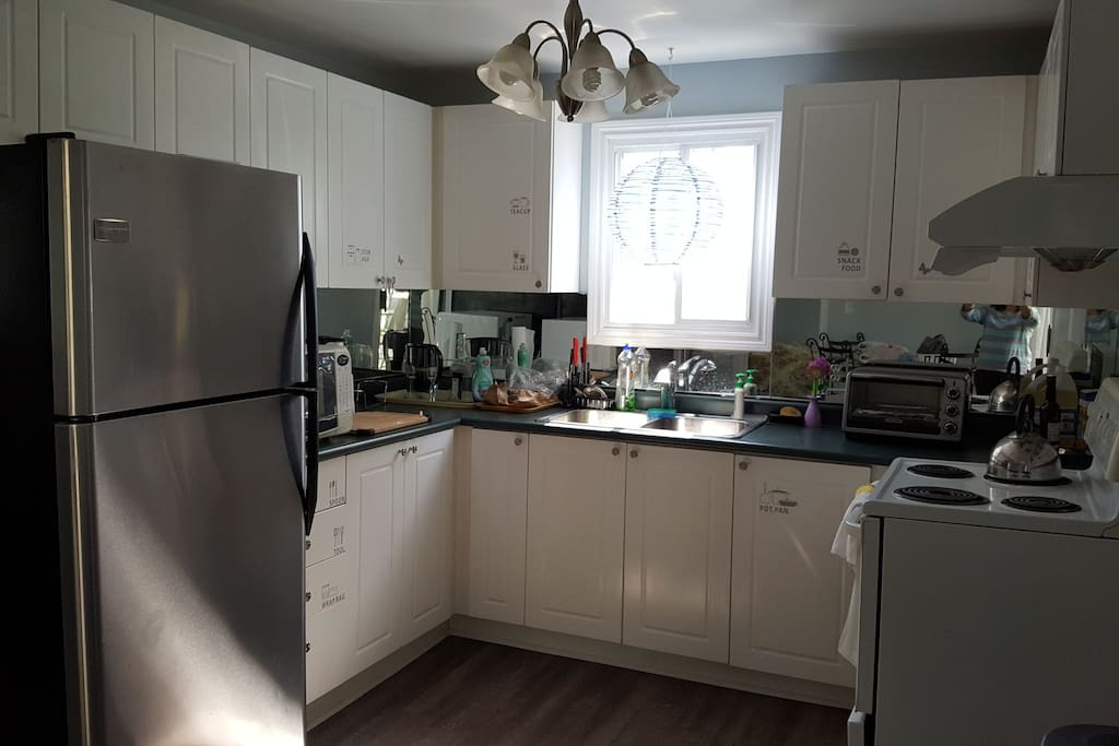 kitchen with stove, toaster oven, microwave, kettle, fridge