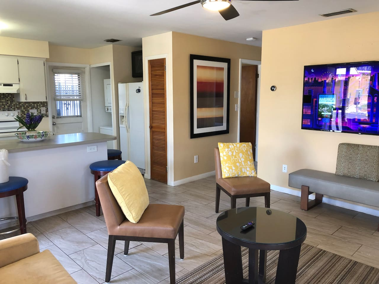"""Family room area with a 65"""" TV and plenty of seating."""