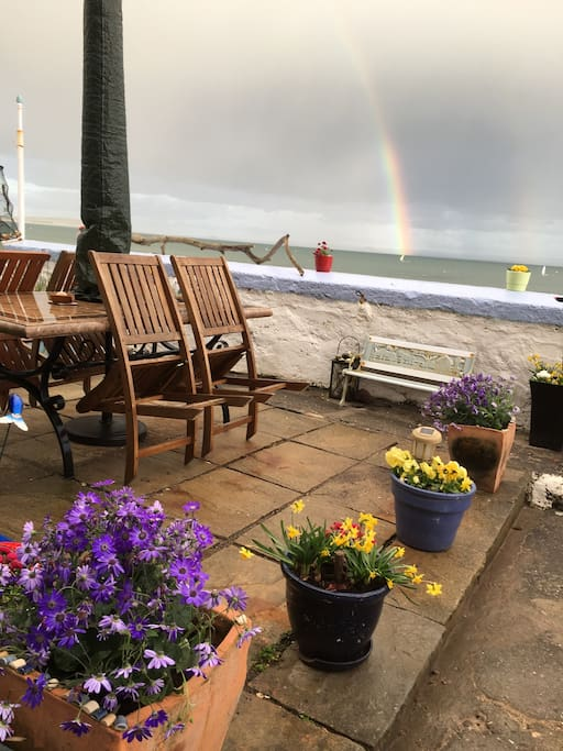 Rockpool Cottage patio table and a beautiful rainbow over the sea. Perfetto!