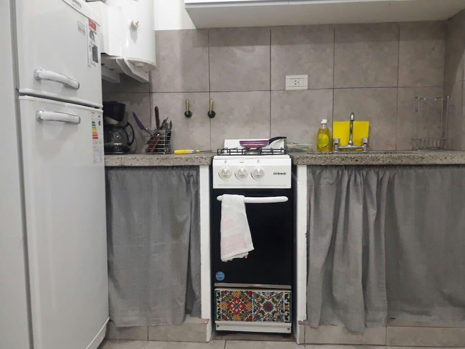 Cocina con horno, vajilla y heladera con frezzer