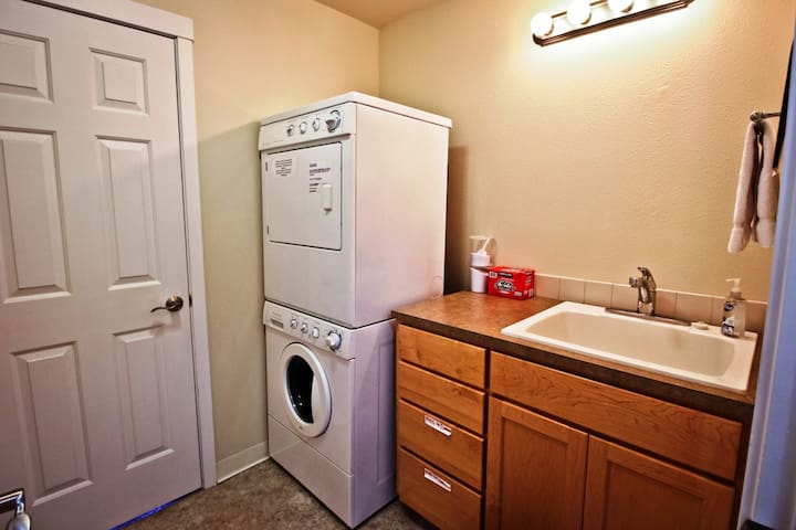 Laundry room with stackable washer/dryer and sink area.