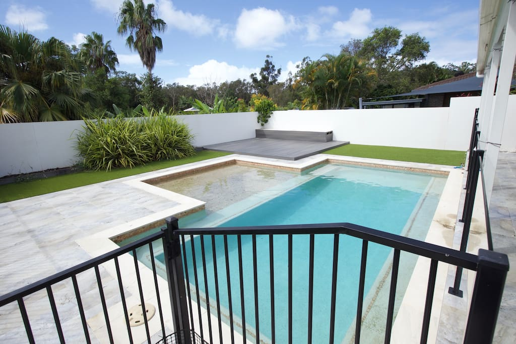Beach entry pool with large deck and grassed area