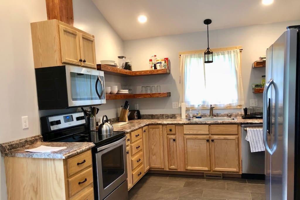 Full kitchen with dishwasher, fridge, oven, stove, microwave.