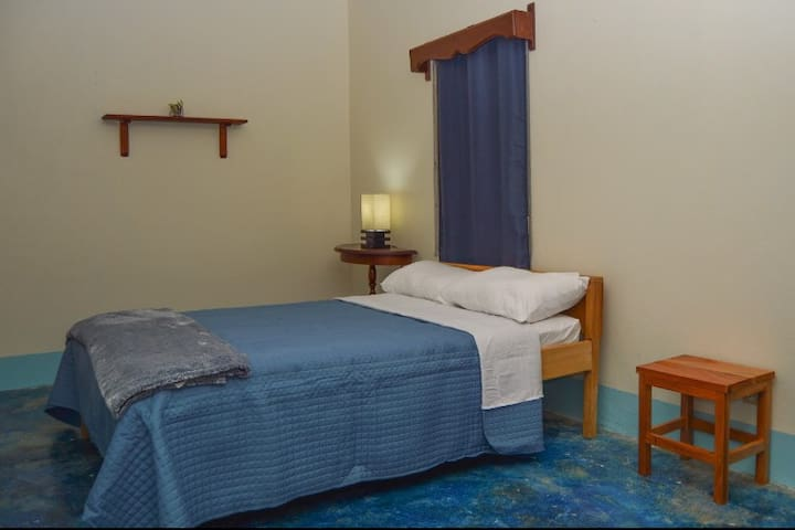 Your room, Room 1 is our ocean room, it has one queen sized bed that can comfortable hold two persons. This room is equipped with two side tables, one lamp, one chair and a wardrobe.