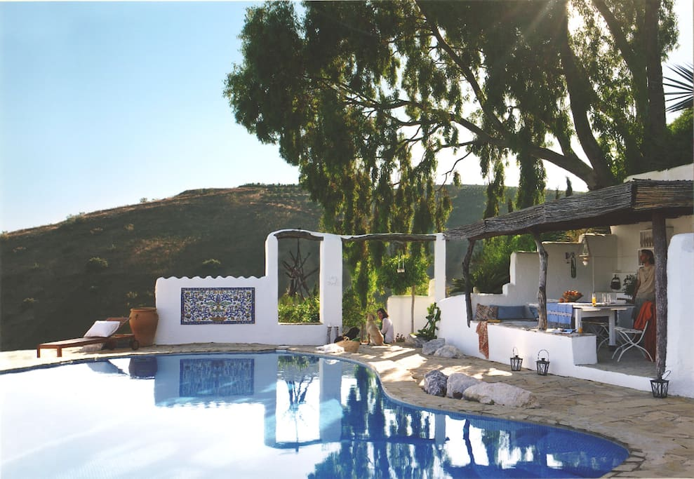 The private pool features a covered summer kitchen with barbecue and dining area, refrigerator and lounge areas.