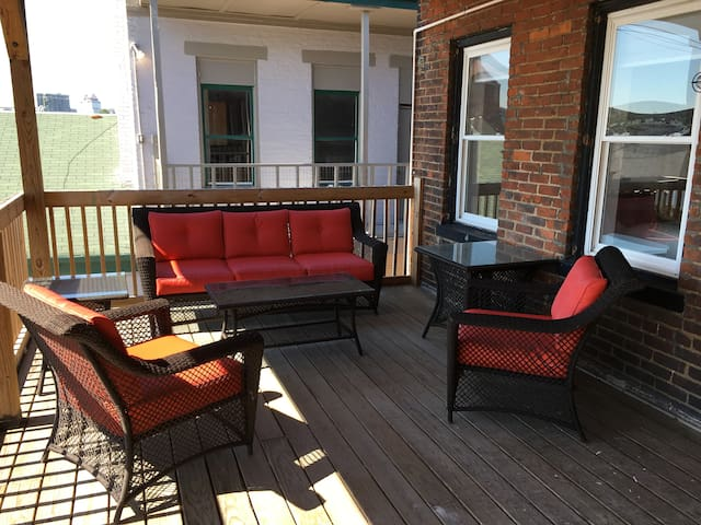 A private deck with large fans to relax while staying cool. This is also your rear entrance, with parking lot below.