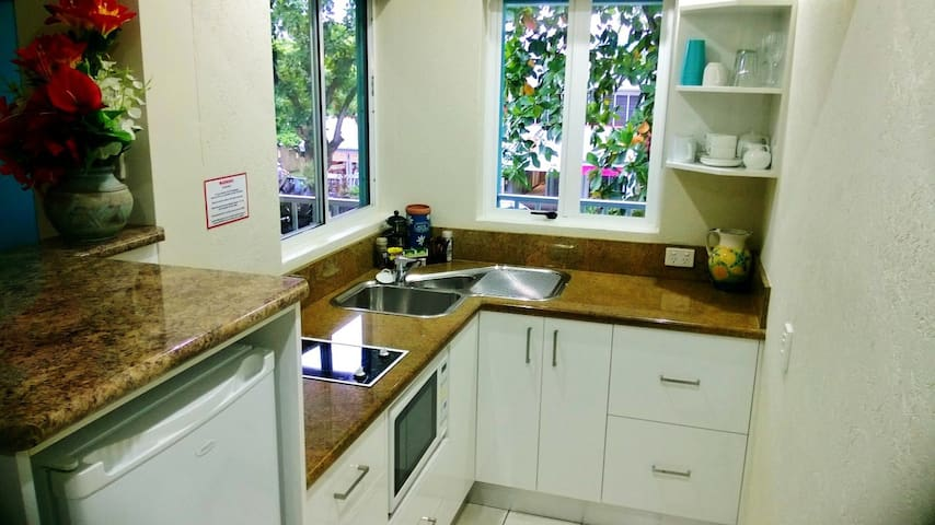 The lovely kitchen with ceramic cooktop, bar fridge, pot draws and more.