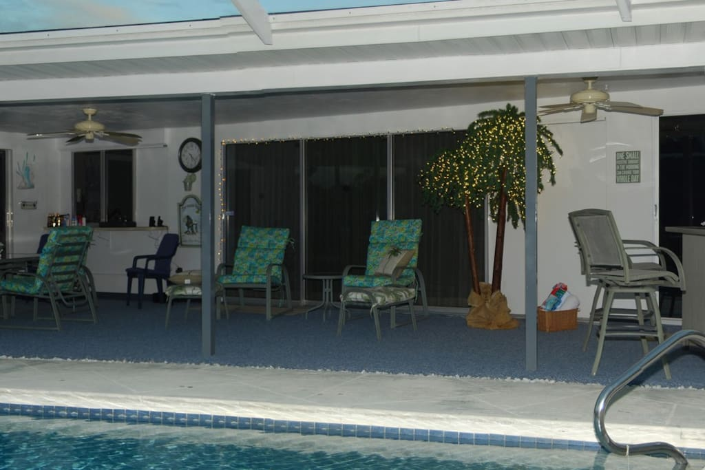 Large Lanai with dining set next to kitchen pass-through, bar and lounge chairs