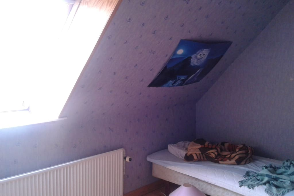 A bedroom on the top floor, complete with cat pictures and everything.
