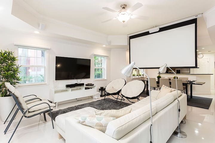 Living room includes projector with pull-down screen