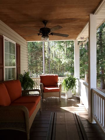 Large porch surrounded by towering pine trees - perfect for relaxing and listening to the birds or watching the dogs chase squirrels..