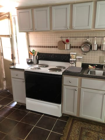 Kitchen with full electric stove, pots & pans, dishes, utensils