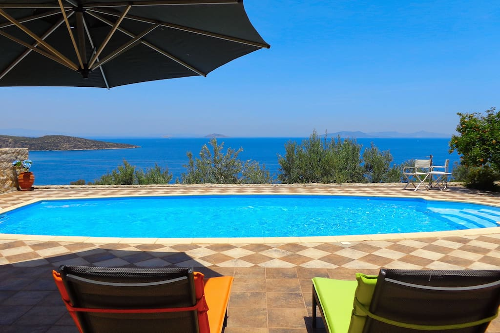 Swiming pool, chaise lounge chairs and outside furniture next to the pool and garden along the beautiful panoramic view