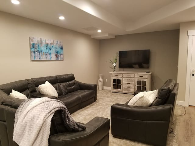 Living Room with smart flat screen TV & recliner couches.