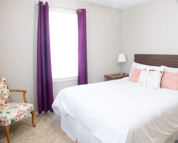 Back bedroom has another queen bed, two nightstands with alarm clock and bedside lamp, dresser, chair and closet.  Room darkening curtains so you can sleep in!