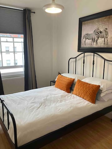 Lovely bright bedroom with double bed hanging space and dressing area