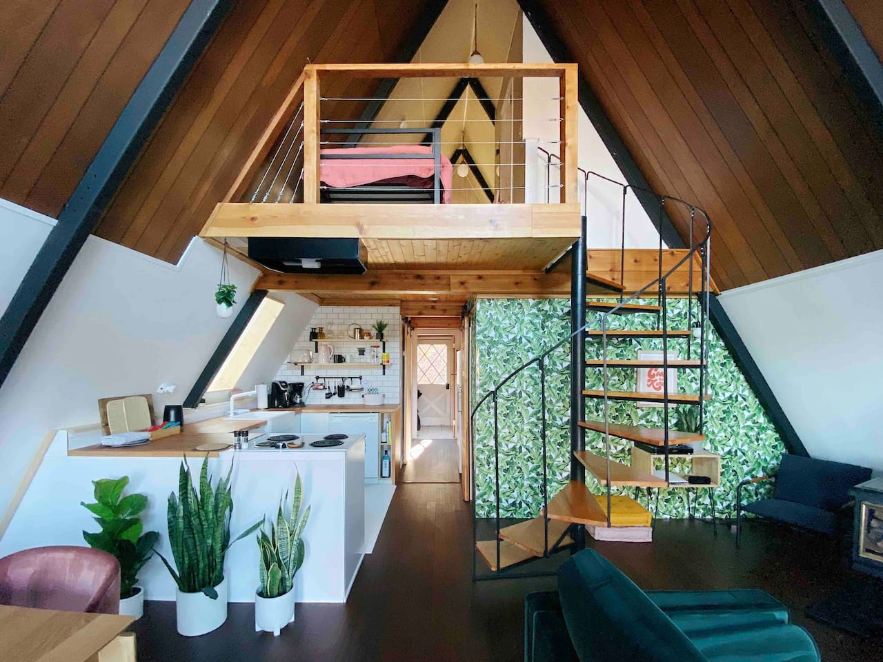 The ultimate A-frame cabin experience: kitchen to the left, pantry on the right. Notice the loft upstairs which overlooks the open living room and dining area.