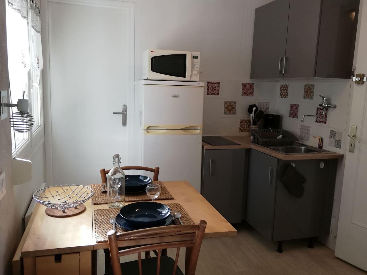 Coin cuisine, table à manger Porte d'accès à la salle de bain et WC