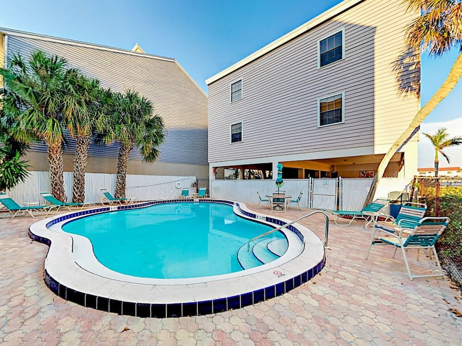 Sparkling shared pool with loungers and an outdoor shower.