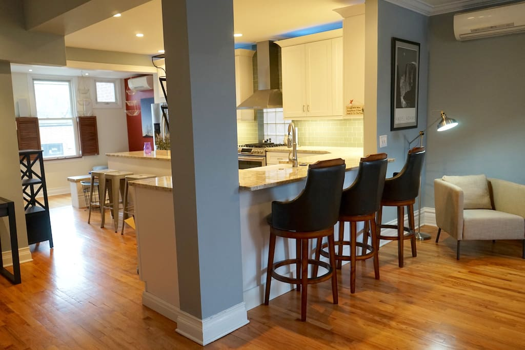 Wide open kitchen with bar stools galore.