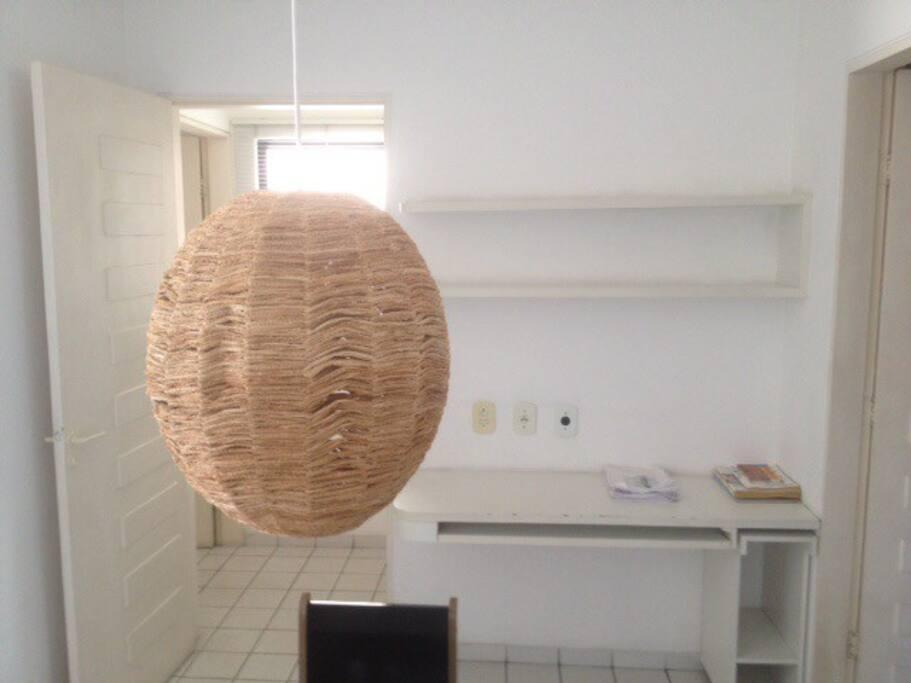 Copa com luminária de folha de bananeira, prateleiras e espaço para room office.