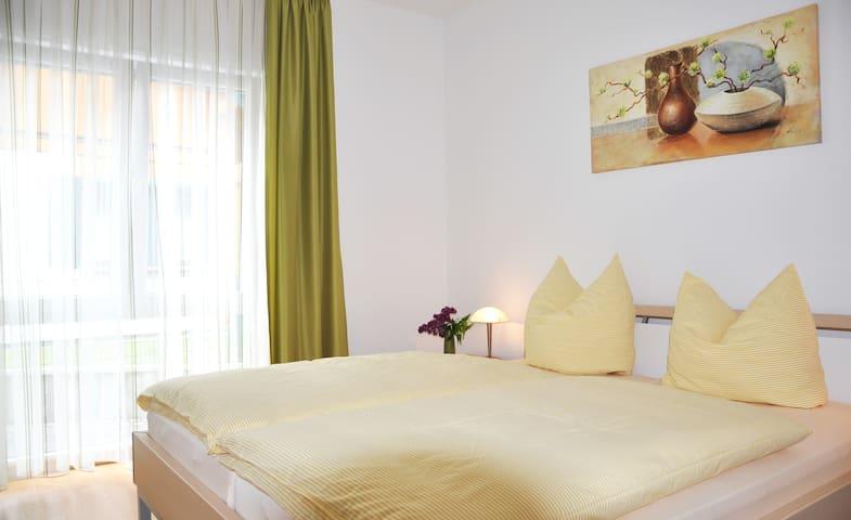 Das Schlafzimmer mit Doppelbett, großer Fensterfront und geräumigem Kleiderschrank.