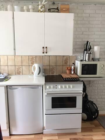 Køkken med komfur, mikroovn og køleskab med lille fryser.
