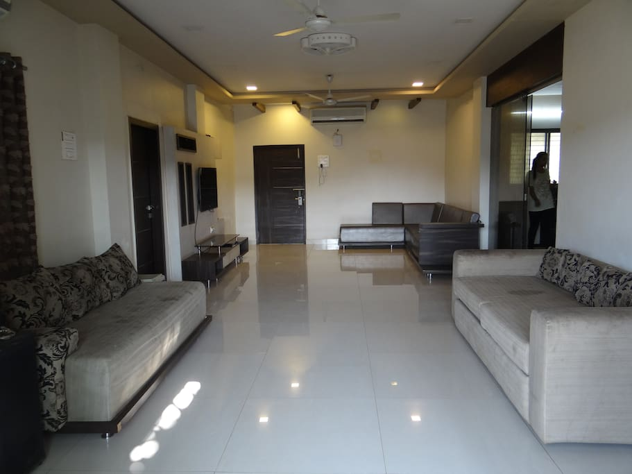 Living room with a double sofa cum bed, LED Tv, home theatre system and seating for upto 8 persons
