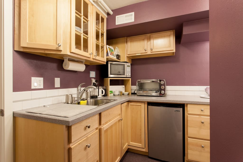 An efficient kitchenette has a microwave, countertop oven, refrigerator, toaster, coffee grinder, French press, and a kettle for hot water.