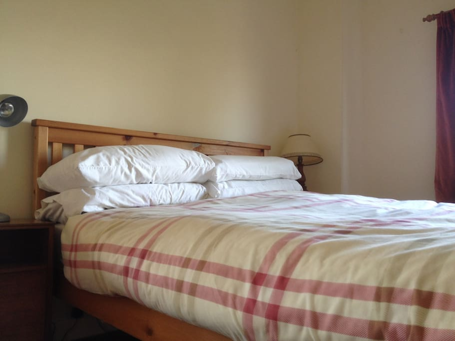 Solid pine double bed in bright and cosy room.