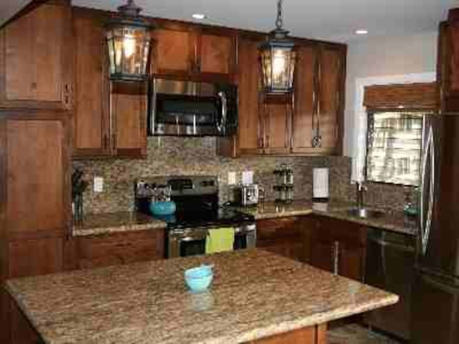 Remodeled kitchen with stainless steel appliances, granite tops, and island dining